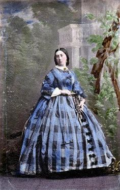 BOWS DOWN THE FRONT --- this time on a dramatic plaid. I'd estimate c1859-60, based on the hair and on this particular trend.