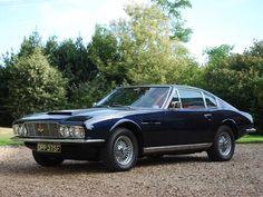 The car turned in on the gravel. It was a DBS, dark blue with matching upholstery. But the Aston was dented and spattered with mud and filthy snow. (1967 Aston Martin DBS.)