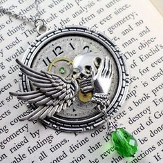 WINGED FACE OF DEATH NECKLACE CABPWF104  $34.00  Antique metal pocket watch face with silver wing, hand, and skull adornments and green glass bead.