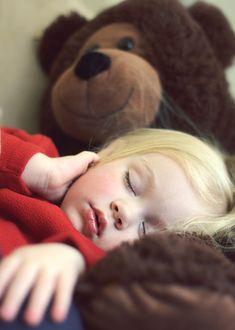 Petite fille endormie sur son ours en peluche / Little girl sleeping on her teddy bear.