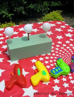 The goal is to knock down the ping pong balls off of the tees with the squirt gun.