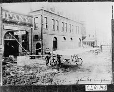 """Athens, 1907. Ben T. Epps with his 1st airplane, built largely from bicycle parts. The building behind him, to the right of the """"Garage,"""" still stands in downtown Athens and is one of the most exciting spots to watch the annual Twilight Criterium bike race. This is Washington St, looking West toward the intersection with Lumpkin St."""