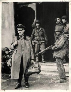 1944- Captured German officer leaving the Hotel Royal in Metz, France under guard of U.S. soldiers.