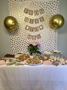 Gold and white bridal shower. Back drop with white polka dot wrapping paper. Food table