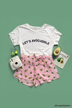 """A PJ set featuring a soft knit tee with a """"Let's Avocuddle"""" graphic, round neckline, short sleeves, and a curved hem, as well as a pair of knit shorts with an allover avocado print, and an elasticized waist with drawstring ties."""