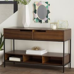 Inspired by midcentury silhouettes, this streamlined console table features 2 drawers and a dark tobacco finish. Top it with a single glowing lamp for a simple, yet stylish, look in the foyer, or add an eye-catching collection of lush succulents, rustic clocks, and candle lanterns to craft a vintaged vignette.