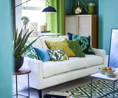 Use several shades of green and offset them with with white furniture and accessories. Palm prints and a geometric rug provide eyecatching patterns.