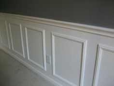Create wainscoting by buying frames from a craft store and painting them to match the wall.
