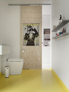 A yellow epoxy floor adds a pop of colour to the bathroom.