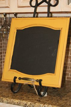 Repaint and distress old cabinet door, apply chalkboard paint in the center. So cool.