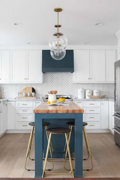 A butcher block countertop accents a blue kitchen island lit by Arteriors Selene Pendants. Blue Kitchen Island, Blue Kitchen Decor, Kitchen Island Lighting, White Kitchen Cabinets, Kitchen Layout, Kitchen Flooring, Kitchen Backsplash, New Kitchen, Dark Cabinets