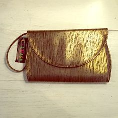 Gold and Brown Clutch NWT! Gold and brown clutch with snap closure. NWT! Strap can be stuffed inside the purse, used as a shoulder strap or a wrestler strap. Zipper pocket inside. Bags Clutches & Wristlets