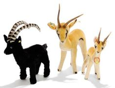 A STEIFF POST-WAR UNLISTED BLACK MOHAIR ROCKY CAPRICORN GOAT, (1322,00?), standing, green and black plastic eyes, pink stitching, felt horns and script button with remains of yellow cloth tag --9¾in. (25cm.) long; and two Yuku Pronghorn Antelope, (1322,00 and 1335,00), golden brown and white mohair, black airbrushing, black plastic eyes, rubber horns, script buttons yellow cloth tags, smaller with chest tag and larger with U.S. import tag, 1962-63 --11½in. (29cm.) and 8in. (20.5cm.) high  (3)