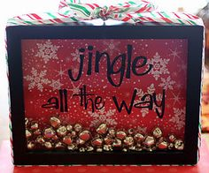 """broken link    black frame wrapped in red, white and green ribbon filled with bells and the back is covered in christmas scrapbook paper and pained on the glass """"jingle all the way"""" or """"jingle bell time, its a swell time"""""""