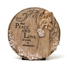 "Peace and Love Angel by Outdoor Décor. $29.99. Keyhole on back for hanging. 12"" Round. A unique indoor or outdoor accent. Original design by © Creative Crickets. Polystone. The beautiful angel upon this stone looks as if she was carved tenderly out of wood. With a bouquet of flowers in her hand, she shares a message of ""May Peace and Love be Yours in Abundance."" Whether used as a stepping stone in the garden or as a plaque to hang upon the wall, this enchanting stone will warm..."
