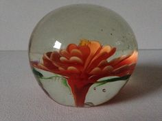 Vintage glass paperweight with pretty orange flower centre.  Crystal clear orb shape glass paperweight with a pretty orange flower centre.  There are green leaves underneath of the flower petals.  An incredibly attractive desk accessory.  No makers mark.  In very good vintage condition.  Approximately 6cm (2) in height, 7cm (3) diameter.  Please note that international courier rates rates fluctuate significantly and the rates given in my shop have to include an allowance for a degree of…