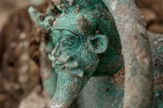 The handles of the bronze cauldron are decorated with the Greek deity Achelous.