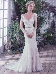This classic sheath wedding dress features embellished illusion lace over jersey & atop a feminine sweetheart neckline and long sleeves with hand-placed lace appliqués. Complete with a dramatic illusion scooped back and scalloped hemline. Finished with covered buttons over zipper closure. Detachable beaded belt sold separately. Roberta by @MaggieSottero.