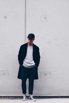 Zwarte pet. Zwart lang vest, met als basis een lichtgrijs t-shirt. Donkerblauwe slim fit chino, opgerold. En lichtgrijze, hoge sneakers.
