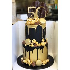 Black and gold two tier with caramel popcorn, macarons, chocolate drip and custom cake topper