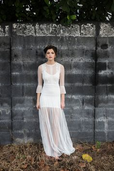 Delicate ivory gauze lace full-length brides dress with overlays of filigree lace and guipure trims. Pleated skirt. Three quarter length sleeves with pleated cuff. Colour match strappy stretchy sculpting slip.