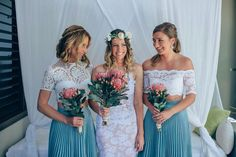 Bridesmaids in dusky blue and white skirts with different white necklines and a pop of pink in their flowers.