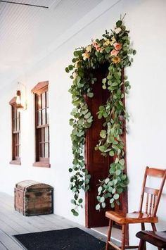 Front Door Decor Wreaths can't have all the fun. This eucalyptus and rose garland frames the door !