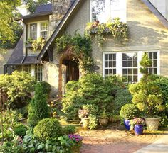 Lush landscaping adds cozy character to this cottage's exterior, from the vines crawling over the arched doorway to overflowing window boxes gracing the upper level. Even though this new shed dormer added to the left side of the house is set back on the roofline, adding a window box to match the one found on the front of the home adds continuity and a splash of color.