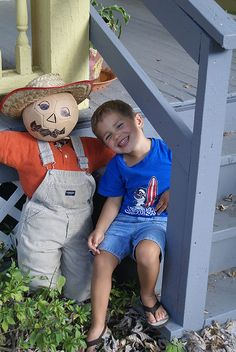 A cute little boy scarecrow using overalls and a basketball.