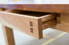 Small details and exposed joinery reveal how much handcraft goes into this simple looking dining table. It has two shallow drawers at each end with a special selection of grain for the drawer fronts. Materials: American Black Cherry CUSTOM ORDERS AVAILABLE/PRICE VIA EMAIL