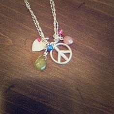 American eagle necklace This layered solve necklace has a peace sign and other fun trinkets hanging on the end of it, including a heart, green bead, pink bead, and thee small colored beads. It has an adjustable clasp. American Eagle Outfitters Jewelry Necklaces