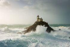 Rough seas swell around a lighthouse in Brittany, France, in this National Geographic Your Shot Photo of the Day.