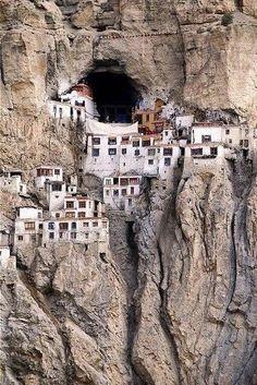Pequeño pueblo en el Tibet, literalmente en las afueras de una gran montaña.