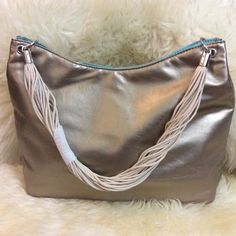 NWOT gold colored bag. Brand new handbag. Length:15 inches, width: 4 inches, height: 9 inches, drop: 10 inches. Pureology Bags Shoulder Bags