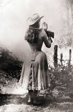 Annie Oakley shooting over her shoulder using a hand mirror, 1888.