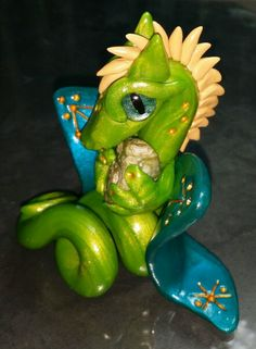 Green dragon with teal wings holding a rainforest jasper.