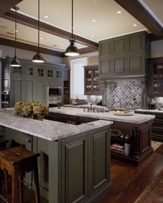 Grand  kitchen with gray and dark stained cabinets. Dark beamed ceiling.  2 Islands!!