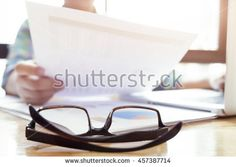 Glasses on office working desktop on business woman working with analysis marketing chart and using laptop to prepare meeting…
