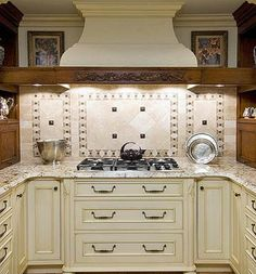 Symmetrical Kitchen Backsplash ~ This symmetrical tile backsplash makes elegance look effortless. Dark accents and patterned squares break up the creamy tile. Diagonally placed tiles diverge from the usual square patterns. Bright lighting from the range hood makes the backsplash a focal point