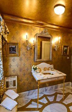 Gold foil Fleur De  Lis walls, gilded ceiling, gold floor tiles, brass (gold) legged pedestal sink for a golden Powder Room