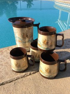 Wonderful set of four Thermo Serv mugs & pitcher with lid. Nautical maps of Caribbean Sea, Atlantic Ocean, Gulf of Mexico with Clippership design. Done in base coat of brown with beige maps & blue, green, & golden yellow ocean images! Bottom stamped made in the USA by Thermo-Serv. Set is in good vintage condition with some minimal wear due to age. Ready for your next nautical or coastal party! Shipped insured! Measures pitcher 8.75 height x 8.5 from handle to spout 5 diameter Mug...