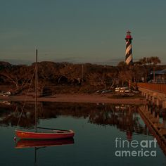 """""""St. Augustine Lighthouse Beach Early Morning Color"""" by Kathi Shotwell. A classic sailboat rests at anchor on glassy water, birds begin their daily flights, the lighthouse greets the morning, and the rising sun casts a subtle pink light over it all. It's a perfect dawn at Lighthouse Park boat beach, Salt Run, Tolomato River, St. Augustine, Florida.  Copyright Kathi Shotwell, all rights reserved."""