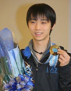 フィギュアスケートのグランプリファイナルで2連覇を達成し、帰国した空港でメダルを手に笑顔を見せる羽生結弦選手=成田空港で2014年12月16日、長谷川直亮撮影