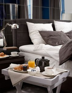 The side of a bed and tray table with breakfast