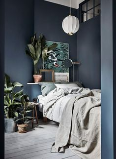 gorgeous masculine bedroom, love the moody dark blue walls, indoor plants and the textured linen bedding