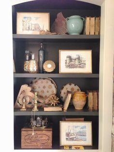 Bookshelf styling elements: vintage ceramics, architectural salavge pieces, old bottles