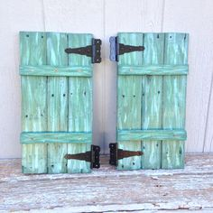 Shutters for my chicken coop, made out of pallet wood and painted dark teal with light blue and light teal streaking.