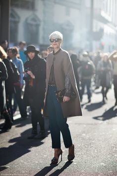 Love the camel cape with deep marine blue ankle pants and animalistic accessories.