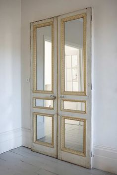 Pair of old doors with mirror inserts against a plain wall or on closet. Love!!!