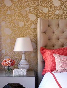 White night table, lamp and jewelry box are complemented by this bold golden floral wallpaper.